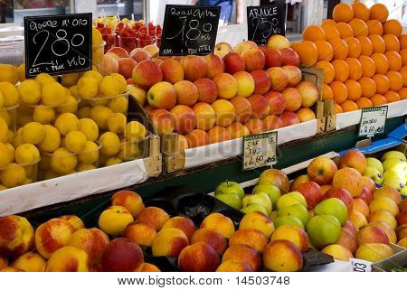 A multicoloured shelf of fresh fruits of a greengrocer