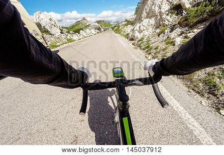 Cyclist on mountainous road in a sunny day. Cycling in Dolomites Passo Valparola. POV Original point of view