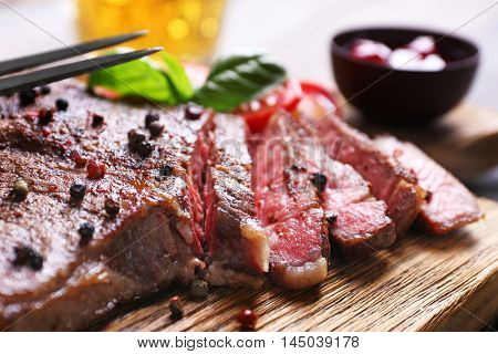 Grilled steak with tomatoes and sauce on cutting board, closeup