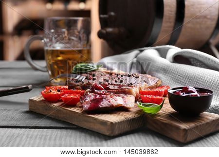Grilled steak with sauce on cutting board and mug of beer on table