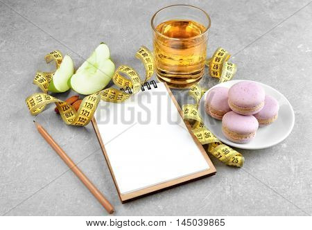 Notepad, measuring tape, juice and sweets on grey background