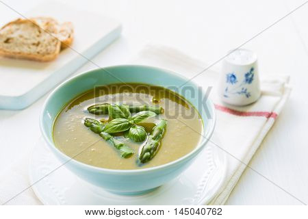 Close up of asparagus soup in a bowl with basil bread and salt shaker