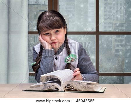 Girl with the book is sad. Outside the window snow winter. The concept of sadness loneliness adolescence overweight complexity