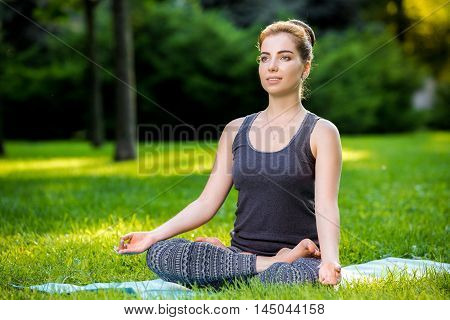 Meditating woman in meditation in city park in yoga pose. Girl relaxing with serene relaxed expression outside in summer. Beautiful young Caucasian female model.