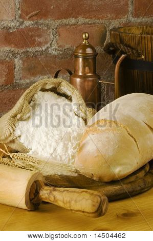 Rural kitchen with loaf of bread, rolling pin, wheat ears, oil and a sack of flour