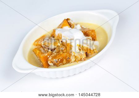 Sweet pumpkin in coconut milk on white background.