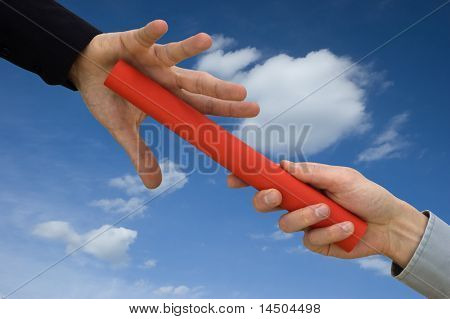 One businessman passing a red baton to another businessman over blue sky. Symbol of teamwork, helping and partnership.