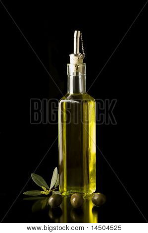 Bottle of fine Italian extra virgin olive oil with olives and some leaves.