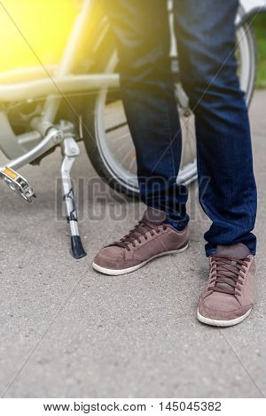 Closeup of mens legs in blue jeans and sneakers and bicycle. Image with lens flare effect