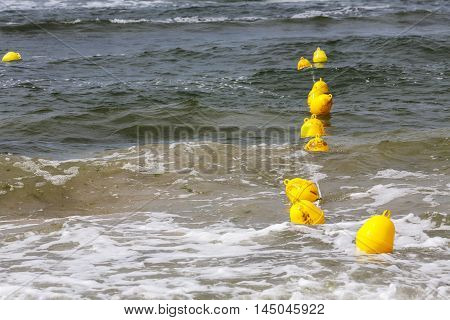 Yellow buoys on the Baltic sea waters define the boundary of the safe swimming at the beach in Kolobrzeg in Poland