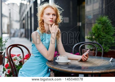 young woman in blue dress with phone in hand at cafe on street