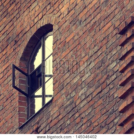 The wall of the old brick building with an open window in the window