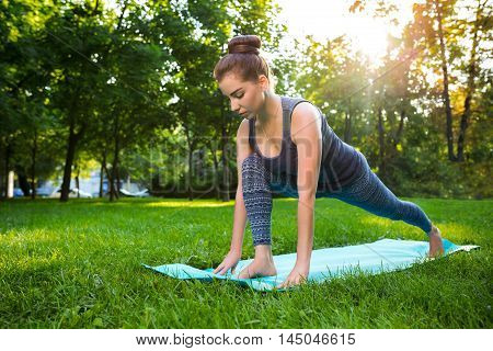 Young fitness woman meditation in a city park.Yoga at sunset in the park. Girl is practicing yoga. Fitness training outdoors. Attractive fitness woman. Workout outdoors. Healthy lifestyle. sun flare