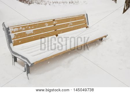 A bench in a park covered in snow