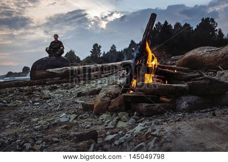 Campfire and silhouette of hiker sitting in a lotus pose on stone.