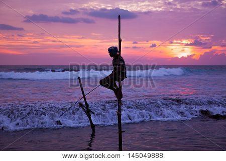 AHANGAMA - NOVEMBER 27 : Still fisherman's fishing fish at sunset on November 27 2015 in Ahangama Sri Lanka