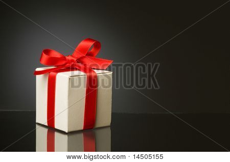 Little white box with red ribbon to celebrate a special Christmas