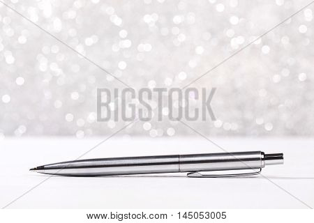 Stylish metal pen lying on white surface, on silver sparkle background.