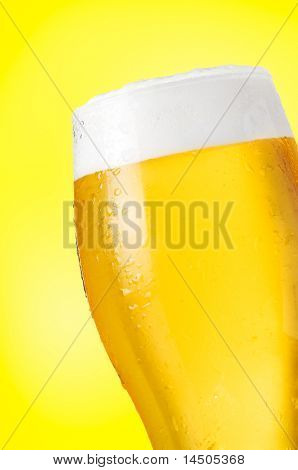 Detail of glass of cold beer with water drops on yellow background