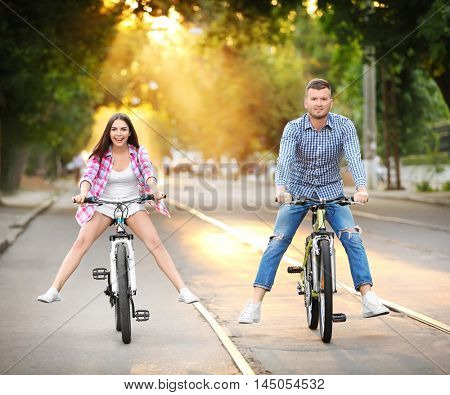 Young lovely couple riding bicycles on street