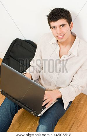 Happy young man working on his laptop with casual clothing and bag