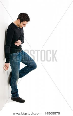 Full length portrait of young laughing man standing against white wall with copy space for your text