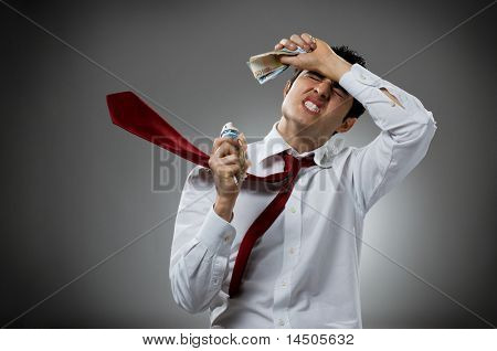 Desperate young businessman with blowing necktie and his bunch of money. Recession and crisis concept!