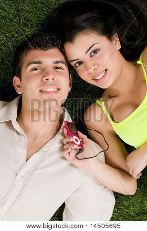 Young couple listening music on a mp3 player while relaxing outdoor