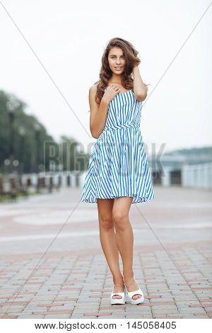 Spring Beautiful Woman In Summer Dress Walking In City River Park Enjoying Weekend. Playful And Beau