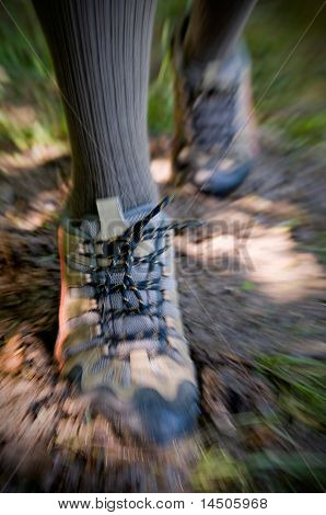 Outdoor trekking in a muddy path with technical shoes. On camera panning and zooming technique to emphasize the action