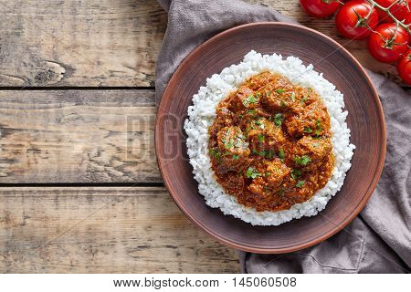 Traditional Madras butter Beef spicy garam masala slow cook lamb food with rice and tomatoes in clay dish on vintage wooden table background. Delicious India culture restaurant dish.