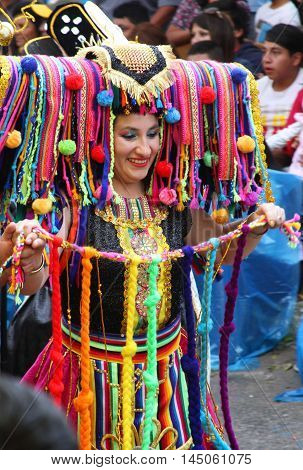 Cajamarca Peru - February 8 2016: Smiling woman in brightly colored costume with headdress marches in Carnival parade in Cajamarca Peru on February 8 2016