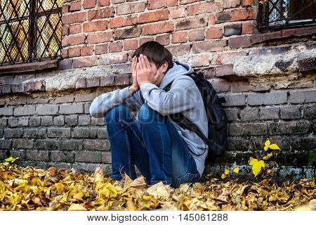 Sad Teenager sit near the Brick Wall of the Old House