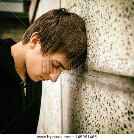 Toned Photo of Sad Teenager by the Wall outdoor