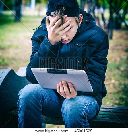 Vignetting Photo of Stressed Teenager with Tablet Computer in the Autumn Park