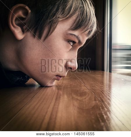 Toned Photo of Sad Teenager looking in the Window