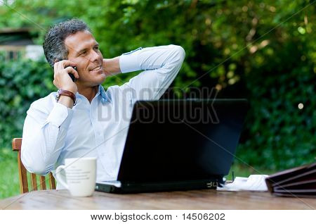 Businessman relaxing outdoor while working with mobile and laptop