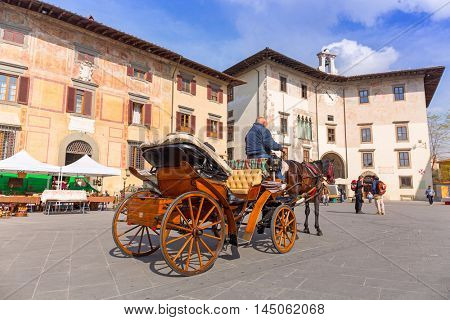 PISA, ITALY - APRIL 11, 2015: Horse carriage ride on the streets of Pisa old town, Italy. Pisa is a city in Tuscany known worldwide for the Leaning Tower, one of the biggest landmark.