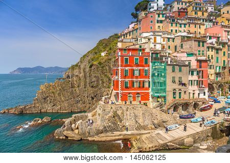 RIOMAGGIORE, ITALY - APRIL 12, 2015: People walking on the street of Riomaggiore village in Italy. Riomaggiore is one of five famous coastline villages in the Cinque Terre National Park, Liguria.