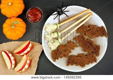 Halloween Party Food With Bat Breads, Broomsticks And Monster Apple Teeth, Overhead Scene On Slate