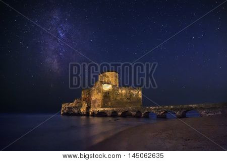 The Milky Way and Torre Astura Italy. An ancient fortified tower that overlooks the sea reduced to a ruin and connected to the beach by a single bridge photographed at night.