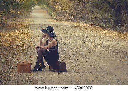 Woman with luggage on an empty road