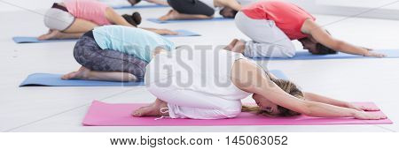 Group of people lying on a floor in a stretch pose during yoga classes panorama