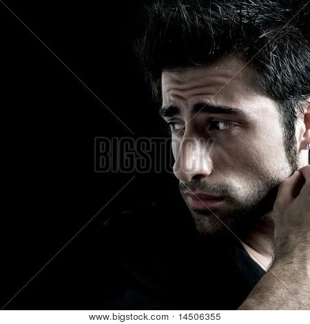 Sad and worried latin man looking away