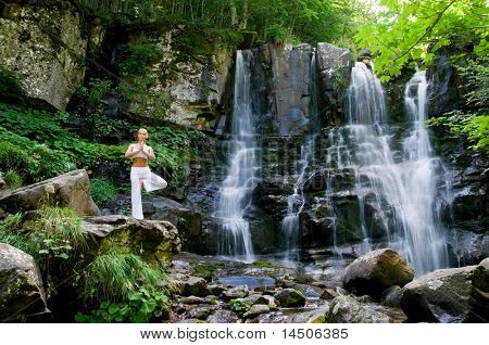 Beautiful young woman doing yoga in a wonderful forest near waterfall