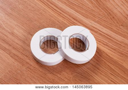 Pair roll's of double sided tape on wooden background