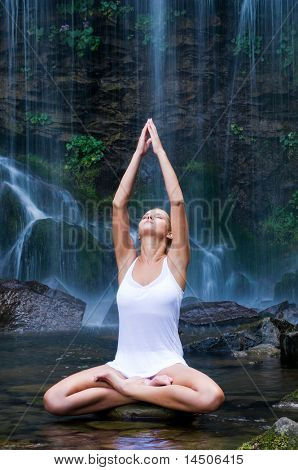 Beautiful young woman doing lotus position yoga in a water pool near waterfall