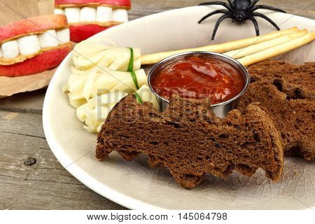 Halloween Party Food With Bat Breads, Cheesy Witch's Broomsticks And Apple Teeth, Close Up Table Sce