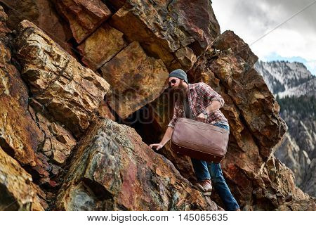 bearded hipster underestimates difficulty of carrying suitcase up a mountain shot with selective focus