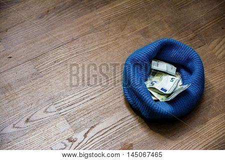 Beanie on Wooden Floor Full of Money Donation